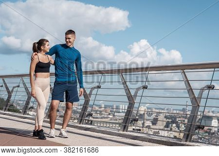 Full Length View Of Happy Young Athletic Woman With Smiling Man Walking Outdoors Together After Spor