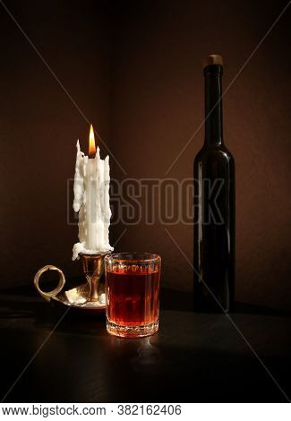 Still Life With Black Bottle, Fruit Liqueur In The Small Glass, And Vintage Candlestick With Burning