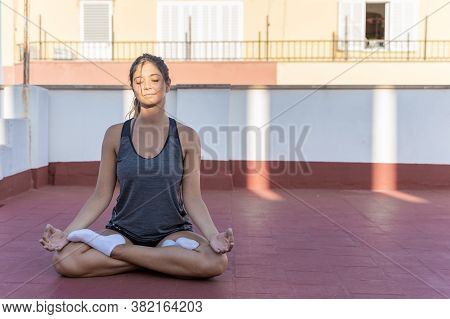 Pretty Young Woman Practicing Yoga, Meditation And Mindfulness On Her Terrace, Lotus Position Or Pad
