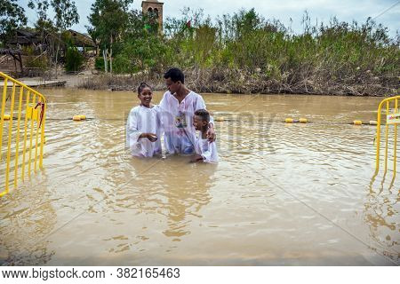 QASR El-YAHUD, ISRAEL - MARCH 2, 2020: Baptism of children. The place of baptism of Jesus Christ on Jordan River. Man in white shirt stand in water and hold the children. The concept of  religius