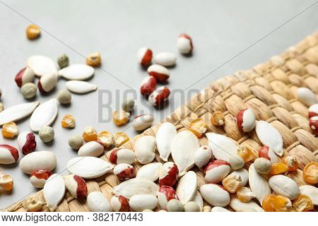 Mixed Vegetable Seeds And Wicker Mat On Grey Background, Closeup