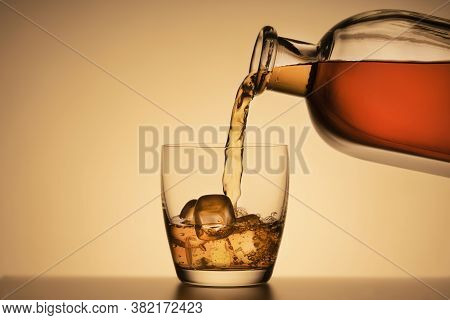 A Glass Of Whiskey On The Rocks. Pouring Bourbon Or Cognac From A Liquor Bottle. Orange Background