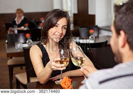 Happy couple in the restaurant toasting themselves with wine glasses