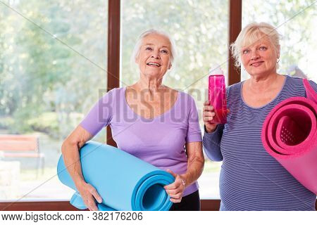 Two vital senior women with yoga mat in yoga class at the fitness center