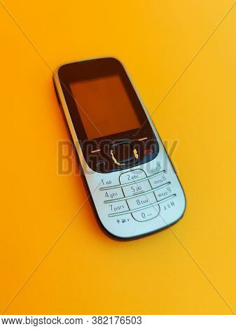 Old Mobile Phone. Cell Phone Isolated On Orange Background, Vintage Mobile Phone, Vintage Style