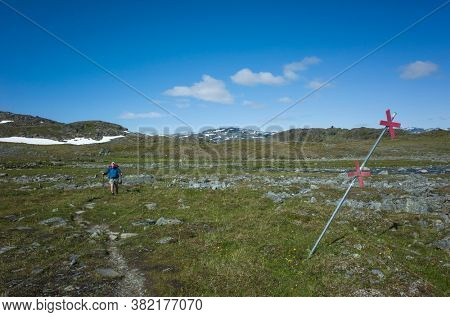 Hiking in Swedish Lapland. Man traveler trekking alone Nordkalottruta or Arctic Trail in northern Sweden. Arctic nature of Scandinavia in warm summer sunny day with blue sky