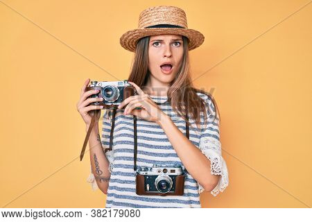 Beautiful caucasian tourist woman holding vintage camera in shock face, looking skeptical and sarcastic, surprised with open mouth