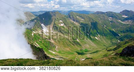 Mountain Scenery Of Romania In Summertime. Grass On The Meadows And In The Valley. Rocks And Snow On