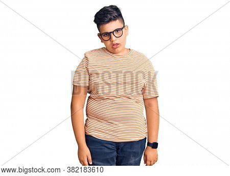 Little boy kid wearing casual clothes and glasses in shock face, looking skeptical and sarcastic, surprised with open mouth