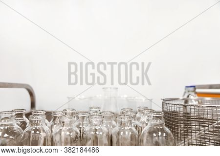 Empty Clear Glass Medicine Bottles Stand On A Cart. Medical Manufacturing Background