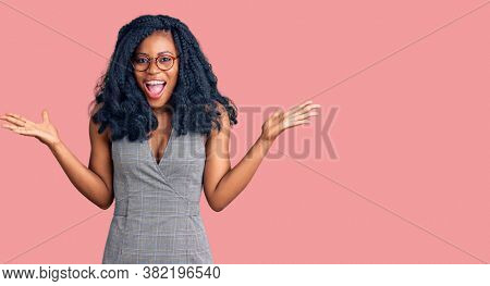 Beautiful african american woman wearing business dress and glasses celebrating victory with happy smile and winner expression with raised hands