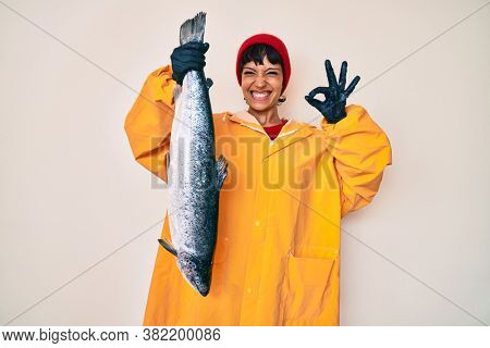Beautiful brunettte fisher woman wearing raincoat holding fresh salmon doing ok sign with fingers, smiling friendly gesturing excellent symbol