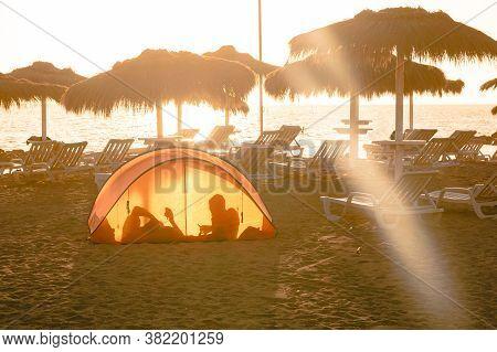 Orange Waterproof Tent Beautiful Sundown. Camping Tent On The Beach Sand Of The Ocean Coastline. Res