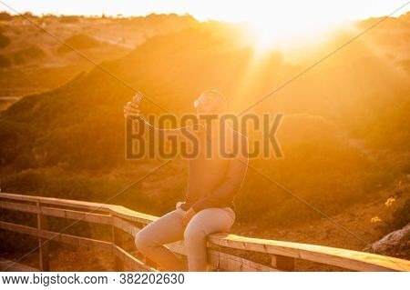 Latin Man Taking Selfies With A Smartphone Over An Amazing Sunset Landscape View