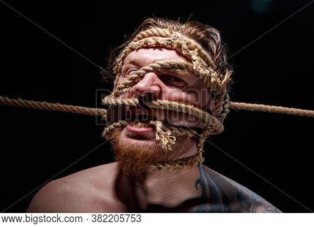 Portrait Of Binded Tattooed Man With Rope On Face