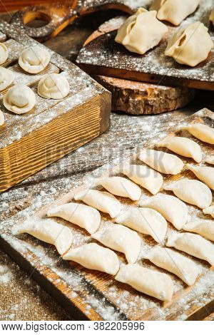 Closeup On Variety Of Semi-finished Dumplings On The Wooden Boards With Flour