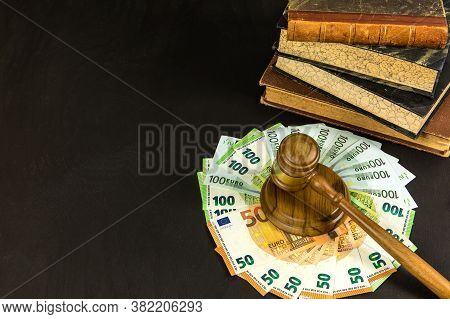Money And Judges Hammer On Wooden Table. Representation Of Corruption And Bribery In The Judiciary.