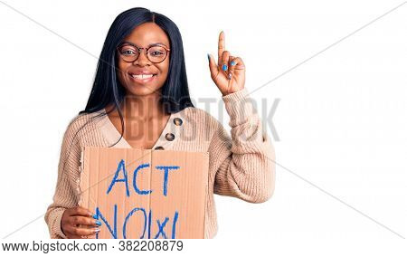 Young african american woman holding act now banner surprised with an idea or question pointing finger with happy face, number one