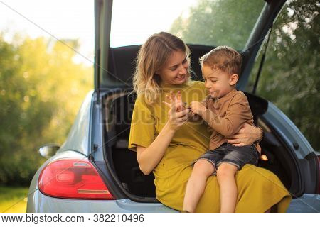 Beautiful Young Mother And Little Son Travelers Sit In Trunk Of Car On Road. Photo About Family Trav