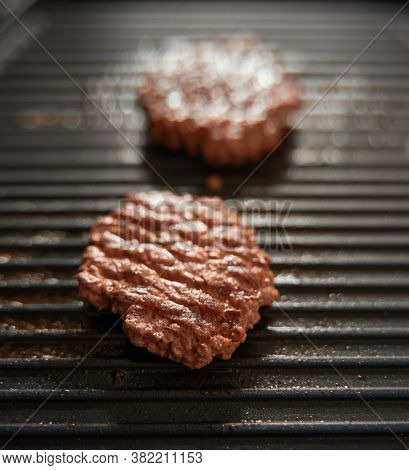 Ground Meat Burger Patties On Griddle Pan Cooking. Dark Background Grille