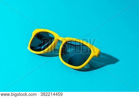 Minimalist Photo Of Stylish Yellow Sunglasses. Sunglasses With Harsh Shadow As Summer Concept. Close