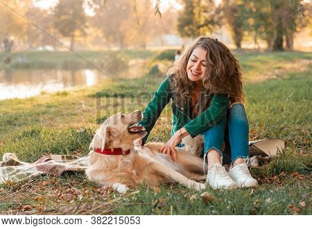 Happy Woman Together With Golden Retriever Dog In A Park Outdoors. Young Female Owner Hugging Pet In