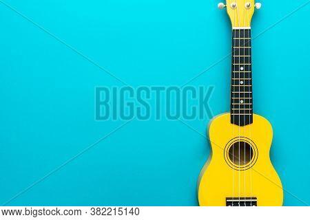Overhead Photo Of Ukulele With Copy Space. Yellow Colored Wooden Ukulele Guitar. Ukulele On The Turq