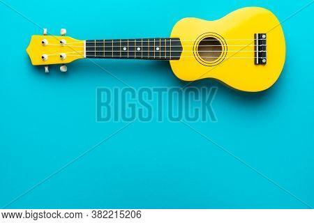 Yellow Colored Wooden Ukulele Guitar On The Turquoise Blue Background. Overhead Photo Of Ukulele Wit