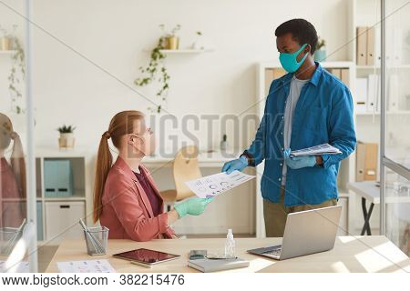 Portrait Of Young Businesswoman Wearing Mask And Gloves Handing Documents To African-american Collea