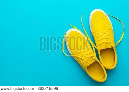 Yellow Sneakers Over Blue Turquoise Background With Copy Space. Left Side Composition Of Vivid Colou
