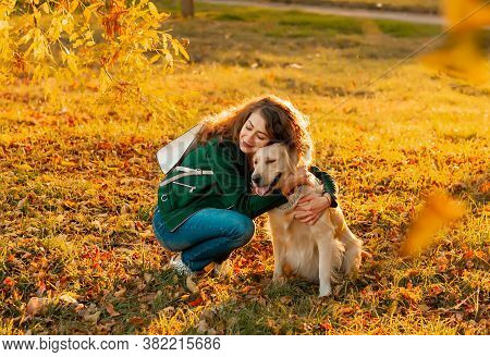 Smiling Woman Hugging Her Pet Golden Retriever Dog Near Face. Golden Retriever Dog Playing With A Cu