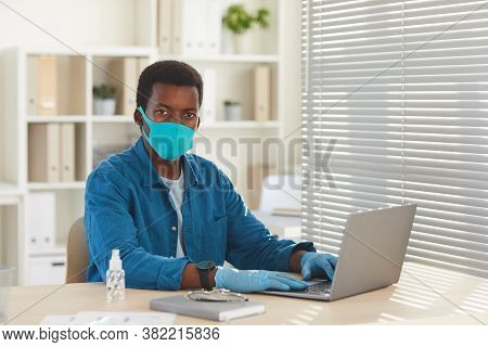 Portrait Of Young African-american Man Wearing Mask And Gloves Looking At Camera While Working At De