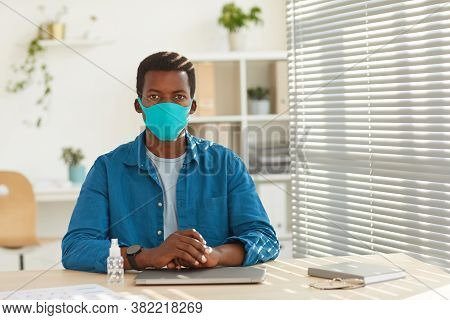 Portrait Of Young African-american Man Wearing Face Mask Looking At Camera While Sitting At Workplac