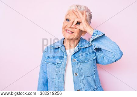 Senior beautiful woman with blue eyes and grey hair wearing casual denim jacket smiling happy doing ok sign with hand on eye looking through fingers