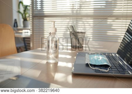 Background Image Of Face Mask And Hand Sanitizer On Empty Workplace Desk In Post Pandemic Office Lit