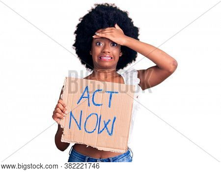 Young african american woman holding act now banner stressed and frustrated with hand on head, surprised and angry face