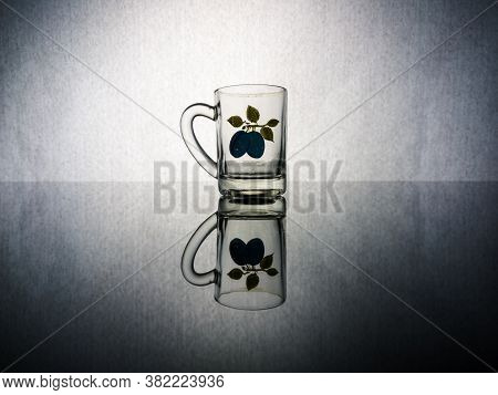 A Small Glass Glass For Brandy With A Picture Of A Plum With A Reflection In The Glass Against The G