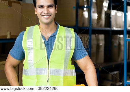 Portrait of Indian asian warehouse worker with safety vest stand and hold yellow helmet in warehouse distribution center environment. Using in business warehouse and logistic concept.