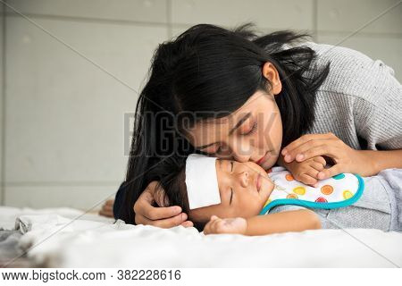 Asian Young Mother Take Care Male Baby Gotten Fever Illness In Bedroom With Copy Space