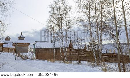 Ancient Wooden Huts In Winter. Snow-covered Village, With Its White Birches