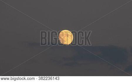 August Orange Full Moon Hides Behind Blue Clouds Background, Texture.
