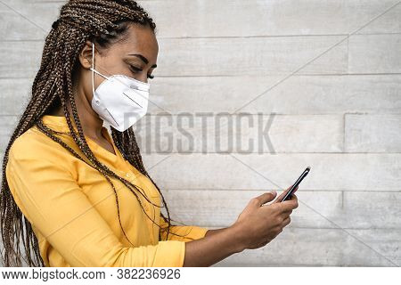African Woman Wearing Face Medical Mask Using Mobile Smartphone - Young Girl With Braids Having Fun