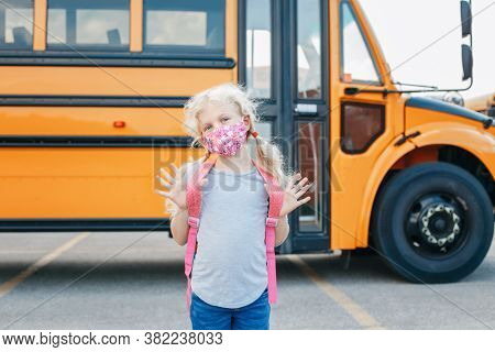 Happy Caucasian Girl Student Wearing Face Mask Near Yellow Bus. Kid With Personal Protective Equipme