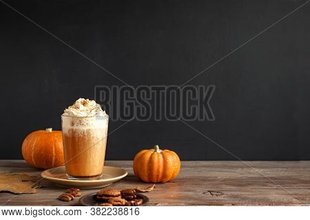 Pumpkin Spice Latte. Seasonal Coffee Drink And Organic Pumpkins Near Black Wall, Copy Space.