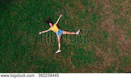 woman lying on a meadow with open arms and legs