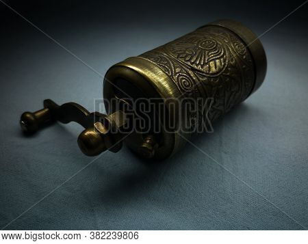 A Small Brass Hand-held Coffee Grinder Embossed On Textiles Against Darkness. Traditional Turkish Ha