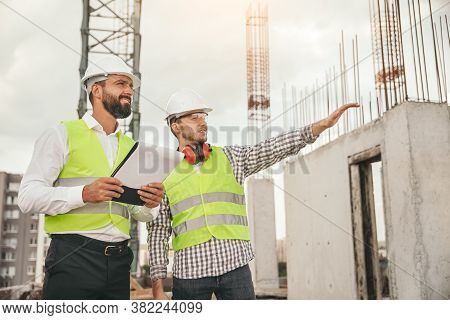 Low Angle Of Professional Engineer Pointing Away While Standing Near Unfinished Building And Discuss