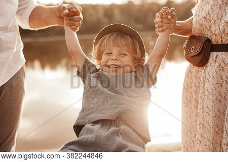 Crop Mother And Father Swinging Happy Boy While Standing On Lake Shore During Sunset In Countryside