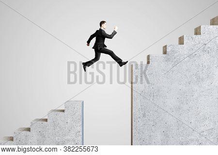 Young Businessman Jumping On Stairs On Gray Background. Success And Growth Concept