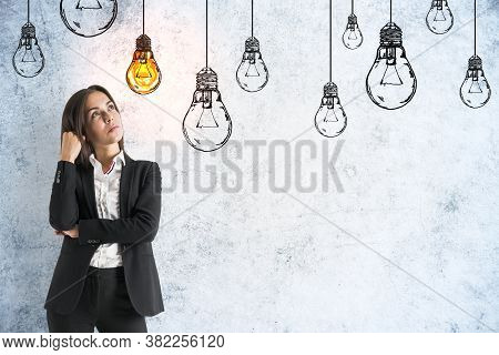 Businesswoman Thinking And Drawing Yellow Lamps On Grey Concrete Wall. Innovation And Leadership Con